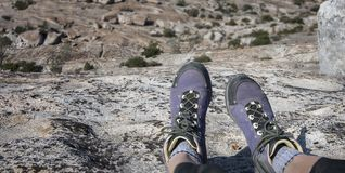 Wandelaarzitting op rotsklip stock foto