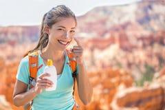 Wandelaarzonnescherm - Vrouw wandeling het zetten sunblock Royalty-vrije Stock Afbeeldingen