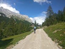 Wandelend meisje in de bergen op een lange weg met bomen royalty-vrije stock afbeeldingen