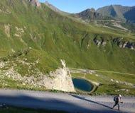Wandelend meisje die een weg in de bergen met een lange schaduw lopen royalty-vrije stock afbeeldingen