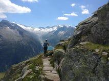 Wandelend meisje die met rugzak van de mening van de bergen en het meer genieten stock afbeeldingen