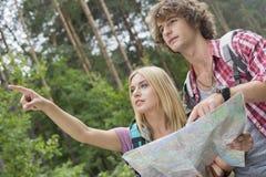 Wandelend paar die met kaart over richting in bos bespreken stock fotografie