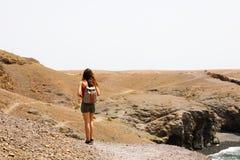 Wandelend wijfje die op Lanzarote martian desertic landschap lopen Achtermening die van jonge vrouw vulkanisch Eiland Lanzarote o stock fotografie