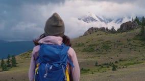 Wandelende of lopende vrouw in mooi bergen inspirational landschap Het meisje bevindt zich en bewondert snow-covered stock footage
