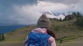 Wandelende of lopende vrouw in mooi bergen inspirational landschap Het meisje bevindt zich en bewondert snow-covered stock video
