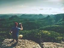 Wandelende mens die beeld van bergen nemen die smartphone gebruiken stock afbeelding