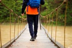 Wandelende mens die rivier in het lopen in saldo op scharnierende brug in aardlandschap kruisen Close-up van mannelijke wandelaar stock afbeeldingen