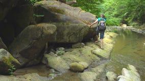 Wandelende mooie vrouw met rugzak die zich langs steenachtige bank die van bergrivier bewegen, op grote kei met groen houden stock video