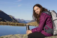 Wandelende vrouw die een pauze op berg maken royalty-vrije stock afbeelding