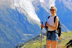 wandelende vrouw die in Mont Blanc-massief dichtbij Chamonix, Frankrijk glimlachen stock foto