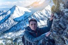 Wandeling met een rugzak die op rotsachtige rotsen tot de bovenkant op de achtergrond van sneeuwbergen kruipen De voltooiing van  stock afbeeldingen