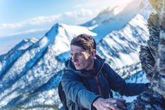 Wandeling met een rugzak die op rotsachtige rotsen tot de bovenkant op de achtergrond van sneeuwbergen kruipen De voltooiing van  royalty-vrije stock afbeelding