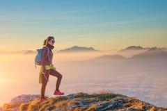 Wandeling op bergrand in het overzees van wolken Stock Foto