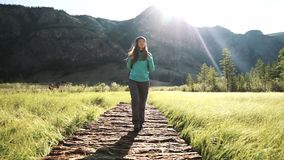 Wandeling Vrouwentoerist die op een brug in de bergen lopen Avontuur in een stijging 50 fps stock videobeelden