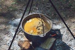 Wandelingspot, Bowlingspeler in het vuur De vissensoep kookt in ketel bij de staak Het reizen, toerisme, picknick het koken stock fotografie