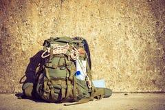 Wandelingsrugzak het kamperen materiaal openlucht op grungemuur Royalty-vrije Stock Foto's