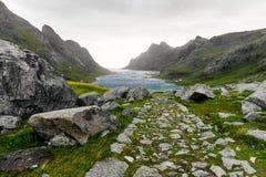 Wandelingssleep die tot een mooie die baai leiden door bergen en een klein dorp dichtbij Bunes-Strand wordt omringd en Vinstad op royalty-vrije stock fotografie