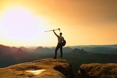 Wanderer auf Spitze Mann in seinem Ziel mit Pfosten in der Hand in einer Luft Stockfotografie