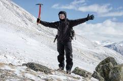Wanderer bleibt auf einem Schneegebirgshügel und genießt schöne Ansicht Stockfotos