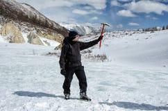 Wanderer bleibt auf einem Schneegebirgshügel und genießt schöne Ansicht Stockfotografie