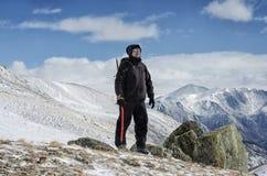 Wanderer bleibt auf einem Schneegebirgshügel und genießt schöne Ansicht Lizenzfreies Stockfoto