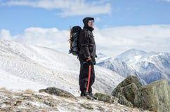 Wanderer bleibt auf einem Schneegebirgshügel und genießt schöne Ansicht Lizenzfreie Stockfotografie