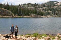Wanderer in den Bergen steht an einem See still Lizenzfreie Stockbilder