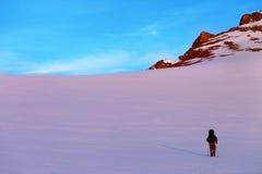 Wanderer in den Sonnenaufgangschneebergen Stockfotos