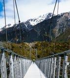 Wanderer, der über Brücke mit Berg im Hintergrund geht lizenzfreie stockfotos