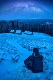 Wanderer, der auf einem Schnee sitzt Stockbild