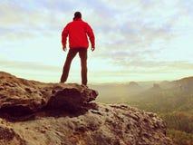 Wanderer, der auf einen Berg steht und Sonnenaufgang genießt Schöner Moment Lizenzfreies Stockfoto