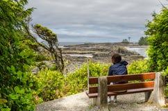 Wanderer, der auf einer Bank entlang einem Naturlehrpfad sitzt Lizenzfreie Stockbilder