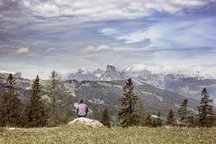 Wanderer, der auf Felsen auf eine Gebirgsoberseite in der alpinen Landschaft sitzt Lizenzfreie Stockfotografie