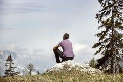 Wanderer, der auf Felsen auf eine Gebirgsoberseite in der alpinen Landschaft sitzt Lizenzfreies Stockfoto