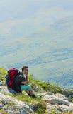 Wanderer, der auf Felsen in den Bergen stillsteht Lizenzfreie Stockfotos