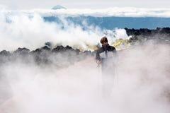 Wanderer, der auf Lavafeld in den Wolken des vulkanischen Dampfs und des Gases klettert Stockbilder