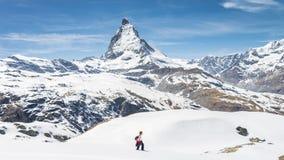 Wanderer, der auf Schnee in Richtung in Richtung Matterhorn-Berg mit weißem Schnee und zum blauen Himmel in Zermatt Verdichterein Lizenzfreies Stockbild