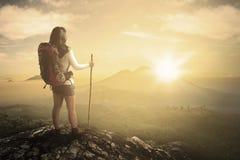 Wanderer an der Bergspitze, welche die Talansicht schaut Lizenzfreies Stockfoto