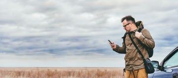 Wanderer, der das intelligente Telefon im Freien verwendet Stockbilder