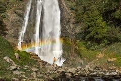 Wanderer, der den szenischen Wasserfall mit Regenbogen genießt stockfotografie