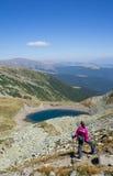 Wanderer, der die Ansicht nahe einem See genießt Stockfoto