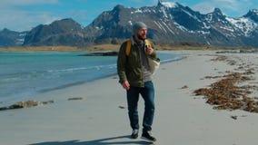 Wanderer, der die grüne Jacke geht auf den Fernsandstrand trägt gelben Rucksack mit großen Bergen und brechenden Wellen trägt stock video