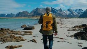 Wanderer, der die grüne Jacke geht auf den Fernsandstrand trägt gelben Rucksack mit großen Bergen und brechenden Wellen trägt stock footage