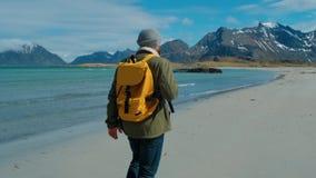 Wanderer, der die grüne Jacke geht auf den Fernsandstrand trägt gelben Rucksack mit großen Bergen und brechenden Wellen trägt stock video footage