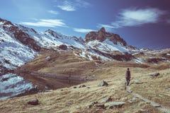Wanderer, der die hervorragende Ansicht der Landschaft der großen Höhe und der majestätischen Spitze des schneebedeckten Bergs in Stockbilder