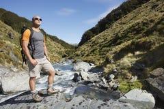 Wanderer, der The Edge von Gebirgsfluss bereitsteht Stockfoto