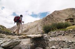 Wanderer, der eine Brücke im Markha Tal, Indien kreuzt Stockbild