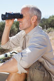Wanderer, der eine Pause auf der Landspur schaut durch Ferngläser macht Stockbilder