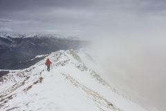 Wanderer, der eine schneebedeckte Kante der Gebirgsenge im Winter klettert Lizenzfreie Stockfotografie