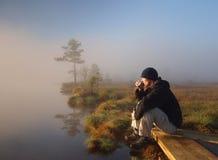 Wanderer, der einen Morgenkaffee in einem Sumpf genießt Stockbild